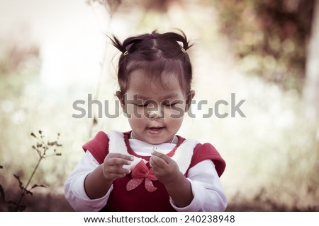 Cute little girl look at small flower on her hand on meadow background in retro style - stock photo