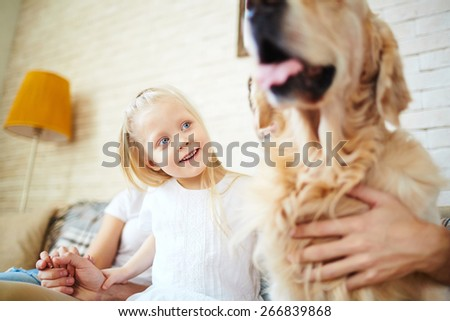 Cute little girl looking at dog