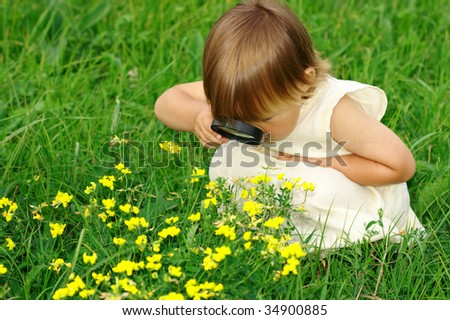 Cute little girl looking at flowers through magnifying glass - stock photo