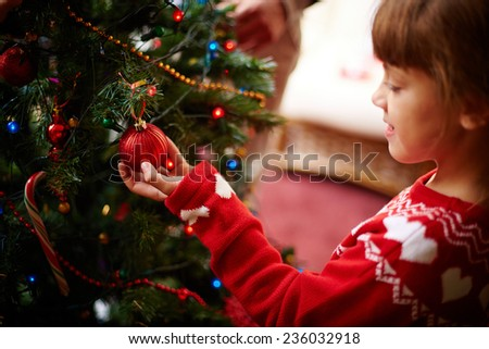 Cute little girl looking at red decorative toy bubble on xmas tree