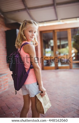 Cute little girl looking behind while holding her launch bag - stock photo