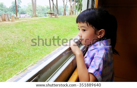 Cute little girl looking out window of a train, selective focus
