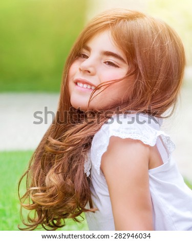 Cute little girl lying down on fresh green grass field; having fun outdoors; relaxing on backyard; happy and carefree childhood - stock photo