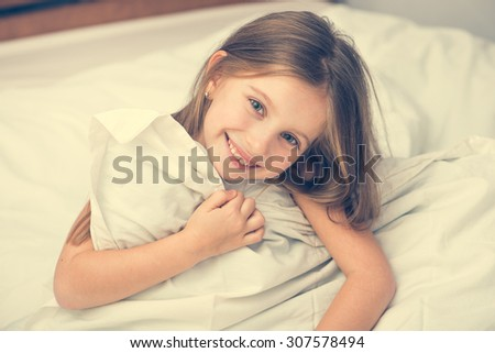 cute little girl lying in a bad under a white blanket - stock photo