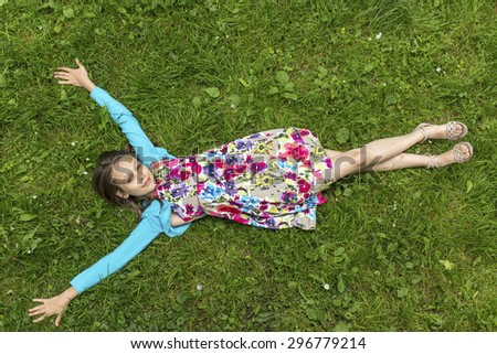 Cute little girl lying on the grass, arms outstretched, top view. - stock photo