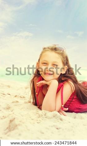 Cute little girl lying on the sand near the sea - stock photo