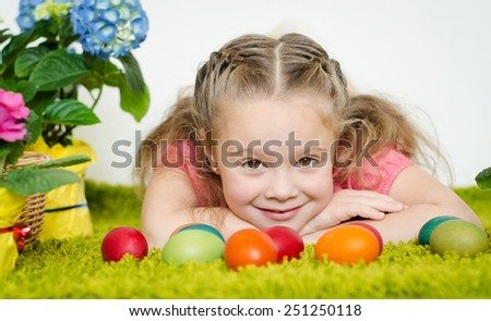 Cute little girl lying with easter eggs and flowers on green carpet  - stock photo