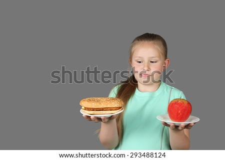 Cute little girl makes choice between hamburger and apple isolated on dark gray background with copy space/place for text message - stock photo