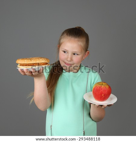Cute little girl makes choice between hamburger and apple on gray background - Fast food, diet and healthy eating concept - stock photo