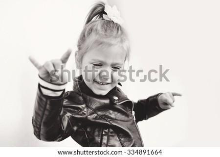 cute little girl making a rock-n-roll sign - stock photo