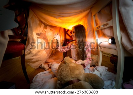 Cute little girl making theater of shadows in bedroom at night - stock photo
