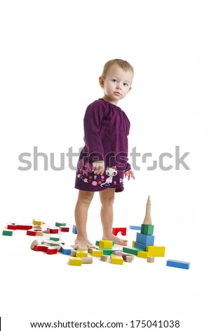 Cute little girl making towers from bricks. Isolated on white  - stock photo