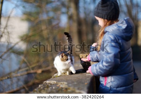 Cute little girl met a cat outdoors on spring day - stock photo