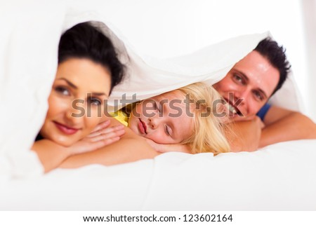 cute little girl napping with parents on bed