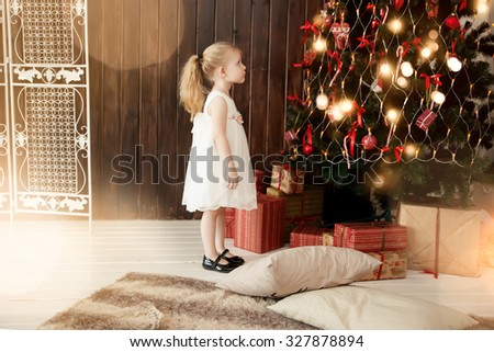Cute little girl near christmas tree - stock photo