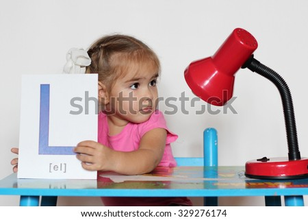 Cute little girl near L letter looking amazed on the red lamp, indoor isolated portrait over the white background
