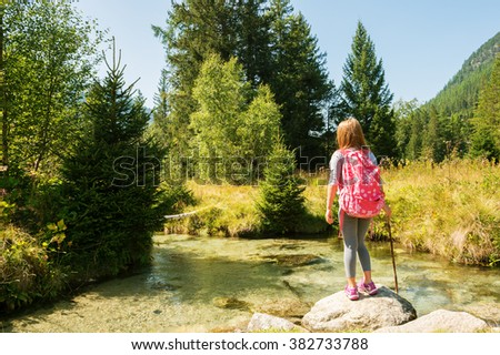 Cute little girl of 7-8 years old hiking in swiss Alps, resting by the river, wearing sport clothes, trainers and backpack, back view - stock photo