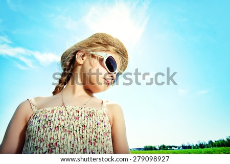 Cute little girl on a meadow in summer day. Happy childhood. Blue sky.