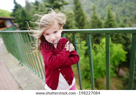 Cute little girl on a very windy day outdoors