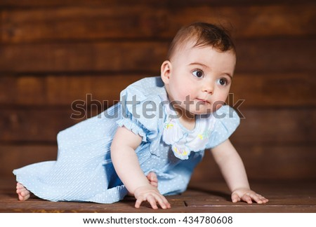 Cute little girl on a wooden background.