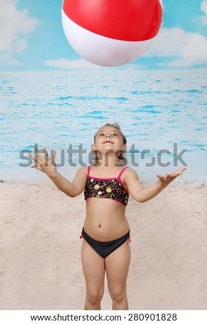 Cute little girl on beach plays with big ball - summer, sun, sea, vacation, childhood concept - stock photo