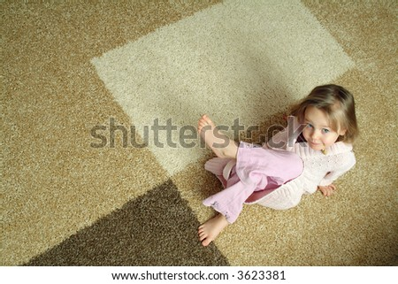 Cute little girl on carpet - stock photo