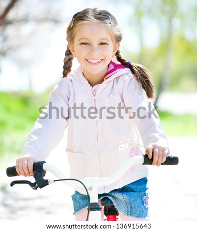 cute little girl on her pink bike on the road. close-up