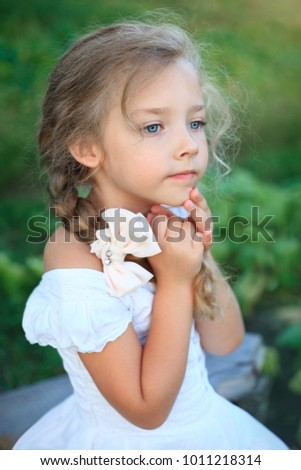 Cute little girl on nature in bright summer day