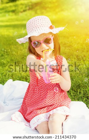 Cute little girl on picnic on sunny summer day sitting drinking juice wearing red dress, hat and sunglasses.  - stock photo