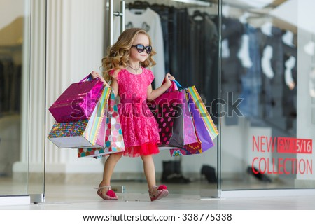cute little girl on shopping. portrait of a kid with shopping bags. child in dress, sunglasses and shoes near shopping mall having fun. shopping. girl.  - stock photo