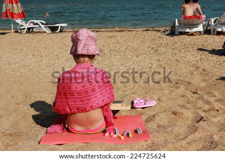 Cute little girl on the beach sitting on the sand, and draws on the blackboard chalk on a hot sunny day on summer vacation and recreation - stock photo