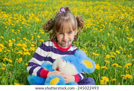Cute little girl on the lawn with dandelions with a toy in her hands