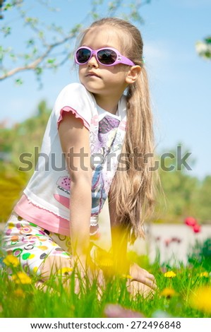 Cute little girl on the meadow in spring day. view of the girl through the grass. preschool girl in the country - stock photo