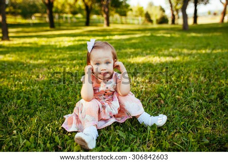 Cute little girl on the meadow in summer day.