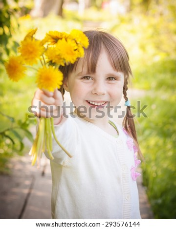 Cute little girl on the meadow in summer day with a bouquet of flowers.