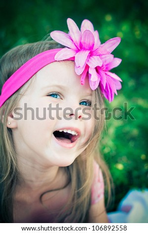 Cute little girl on the meadow laughing - stock photo