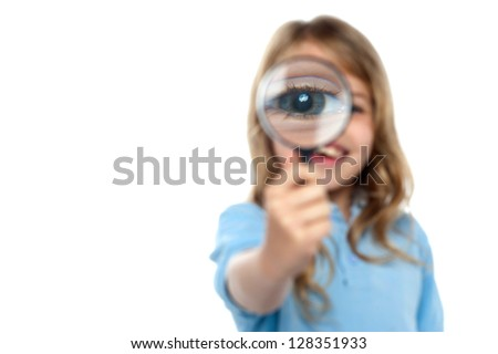 Cute little girl on white background showing her magnified eye.