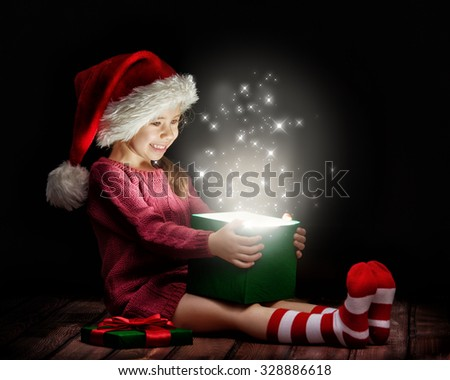 Cute little girl opening a magic gift box. - stock photo