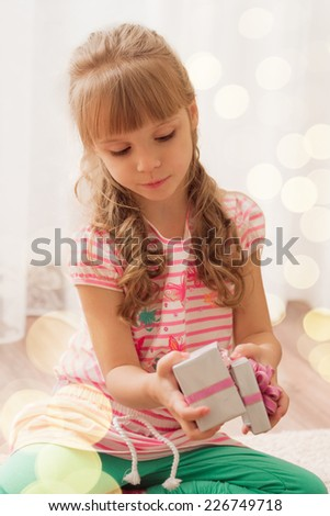 Cute little girl opening a small gift box at home. Holiday lights around.