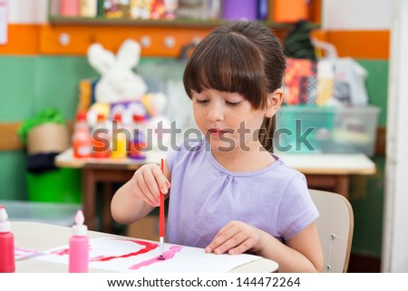 Cute little girl painting at desk in classroom