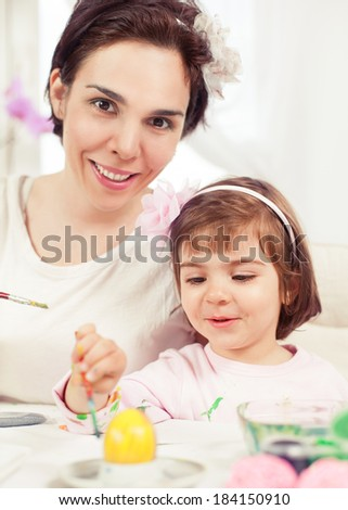 Cute little girl painting Eater eggs with her mommy. Toned image. - stock photo