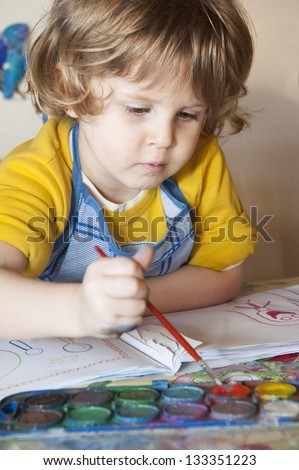 Cute little girl painting in his album