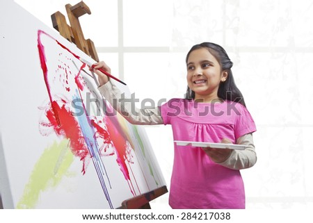Cute little girl painting on canvas during art class