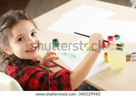 Cute little girl painting picture on home interior background - stock photo