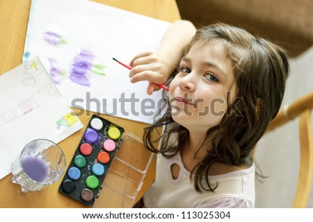 Cute little girl painting with brush in preschool. Child care. - stock photo