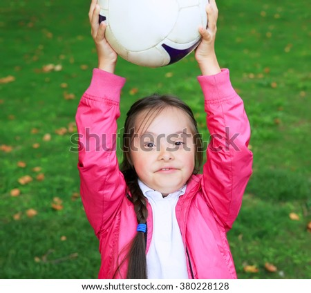 Cute little girl paying in the park with a ball. - stock photo