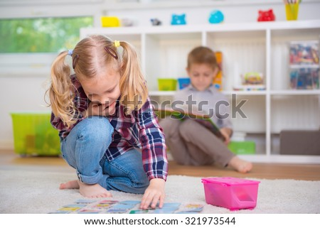 Cute little girl play board game, boy read book - stock photo