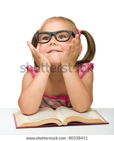 Cute little girl play with book while sitting at table, isolated over white