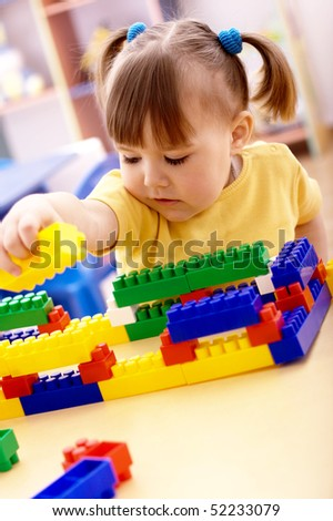 Cute little girl play with building bricks in preschool - stock photo