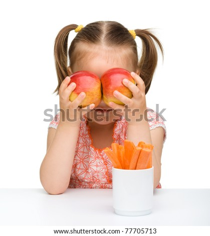Cute little girl play with carrot and apples, isolated over white - stock photo